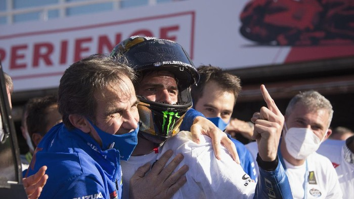 VALENCIA, SPAIN - NOVEMBER 15: Joan Mir of Spain and Team Suzuki ECSTAR  celebrates with Davide Brivio (L) of Italy and Team Suzuki MotoGP  the victory of 2020 championship of MotoGp season under the podium at the end of the MotoGp race during the MotoGP of Comunitat Valenciana at Comunitat Valenciana Ricardo Tormo Circuit on November 15, 2020 in Valencia, Spain. (Photo by Mirco Lazzari gp/Getty Images)