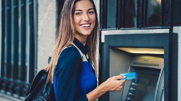 Smiling woman at the ATM ready to withdraw cash money   ++++ Note for the inspector: Credit card is fake ++++