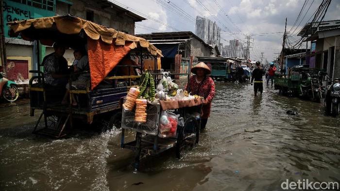 Banjir rob yang merendam kawasan Muara Angke, Jakarta Utara, tak halangi sejumlah warga untuk tetap mencari rezeki. Berikut potretnya.