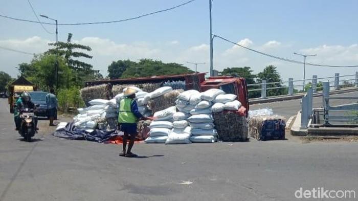 Truk muat plastik terguling saat naik flyover di Desa Masangan, Sukodono, Sidoarjo. Kecelakaan itu membuat muatan tumpah di jalan dan sopir mengalami luka-luka.