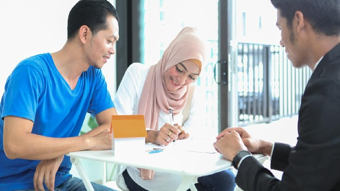 Adult Malay Muslims couple signing documents for house purchase/ rental, sitting in front of a real estate agent.