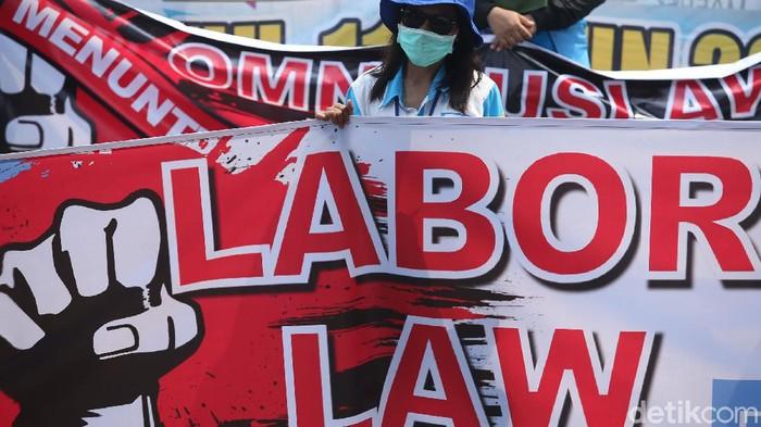 Sejumlah massa buruh dari Serikat Buruh Nasional menggelar aksi di Patung Kuda, Jakarta, Selasa (17/11/2020). Mereka membentuk barikade sambil membawa atribut.