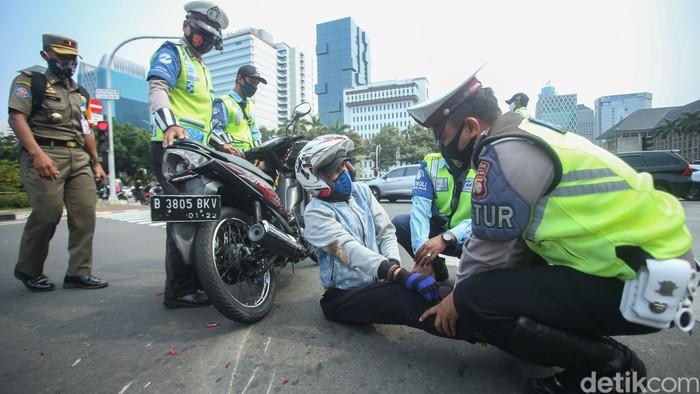 Seorang pengendara motor tergeletak di kawasan Patung Kuda, Jakarta, Selasa (17/11/2020). Usai kecelakaan sejumlah petugas membantu korban.