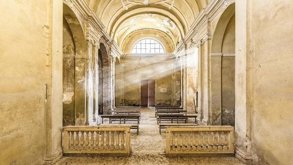 Gereja Abad ke-12, 16, dan ke-20, di Italia. Cahaya masuk di celah celah jendela menyinari dalam gereja yang terdapat susunan kursi-kursi.
