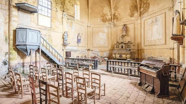 Gereja Abad 13, 14, 16, dan 19, Prancis, Wilayah Nouvelle-Aquitaine. Segalanya tampak masih teratur dengan sempurna. Kursi kayu masih berjejer, batu paving merah muda yang berdebu, alat musik masih berdiri.