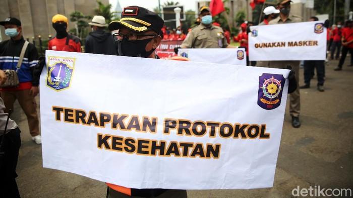 Anggota Satpol PP Kelurahan Gelora mengkampanyekan protokol kesehatan ditengah massa buruh yang demo di depan Gedung DPR, Selasa (17/11/2020). Petugas satpol pp ini mensosialisasikan agar para pendemo menjaga jarak dan memakai masker.