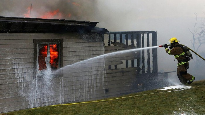 A firefighter tries to put out the final flames of a burned home during the Pinehaven Fire in the Caughlin Ranch area of Reno, Nev., on Tuesday, Nov. 17, 2020. (Jason Bean/The Reno Gazette-Journal via AP)