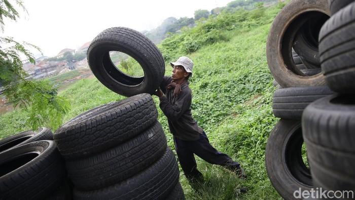 Pekerja merapikan ban bekas di kawasan Jakarta, Rabu (18/11/2020). Limbah ban bekas tersebut dijual dengan harga Rp 200 /kg.