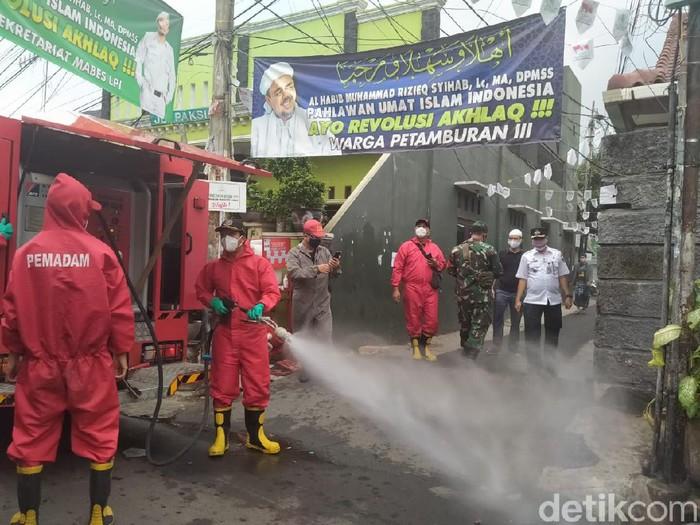 Petugas menyemprotkan disinfektan di sekitar rumah Habib Rizieq di Petamburan, Jakarta.