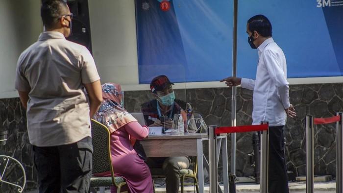 Presiden Joko Widodo (kanan) didampingi Menteri Kesehatan Terawan Agus Putranto (kiri) dan Wali Kota Bogor Bima Arya (tengah) usai  meninjau simulasi  pemberian vaksinasi COVID-19,  di Puskesmas Tanah Sareal, Kota Bogor, Jawa Barat, Rabu (18/11/2020). Dalam kunjungannya, Jokowi meninjau satu persatu tahapan simulasi pemberian vaksin COVID-19, dan juga meminta pada saat pemberian vaksinasi nanti lebih sempurna sehingga aman, cepat dan memperhatikan protokol kesehatan. ANTARA FOTO/Yulius Satria Wijaya/hp.