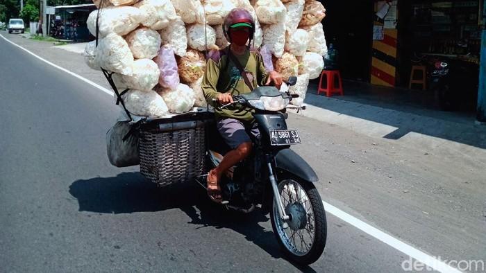 Seorang pedagang yang mengangkut 43 kemasan kerupuk menggunakan sepeda motor melintas di Jalan Yogya-Solo. Meski bahaya, pedagang itu tetap santai melintas di jalan raya.