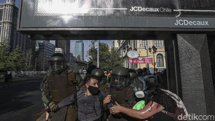 Ratusan orang melakukan aksi protes di Santiago, ibu kota Chile, pada Rabu (18/11) untuk menuntut pengunduran diri Presiden Sebastian Pinera. Tuntutan itu muncul atas praktik penindasan polisi terhadap aksi protes soal masalah sosial di negara itu.
