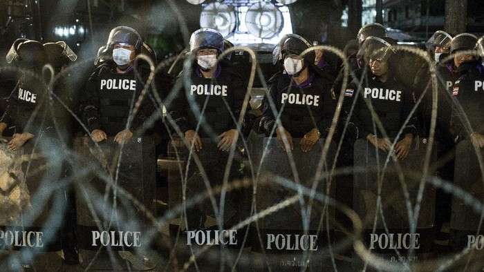 Massa aktivis demokrasi melakukan aksi dan berbaris di markas besar polisi Thailand di Bangkok. Massa melempari dinding kantor polisi dengan cat berwarna cerah.