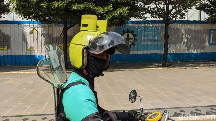 Seorang pengendara ojek online melintasi Jl Thamrin, Jakarta, Kamis (19/11/2020) menggunakan helem unik. Helem tersebut didisain mirip tabung gas elpiji 3 kiloan atau dikenal dengan gas melon.