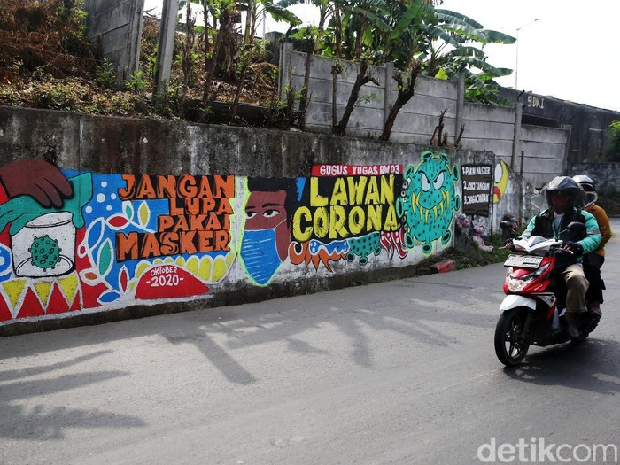 Pengendara melintasi mural bertema COVID 19 di Jalan Cakung Cilincing Barat, Jakarta Timur, Kamis (19/11/2020). Mural masih dianggap menjadi sarana edukasi kesehatan yang tepat bagi warga untuk menjaga diri dari penularan virus Covid 19.