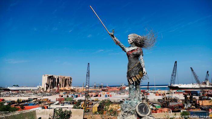 Patung karya Hayat Nazer, yang dibuat dari puing-puing ledakan di pelabuhan Beirut, seperti tampak di latar belakang.