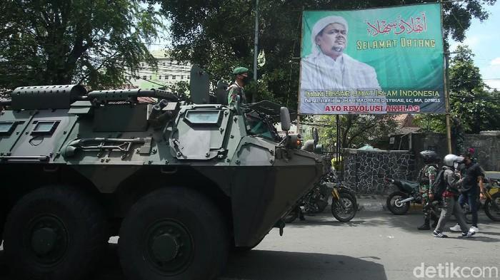 Sejumlah personel TNI menurunkan spanduk besar bergambarkan Habib Rizieq di Jakarta, Jumat (20/11/2020). Mereka turut membawa panser saat beraksi.