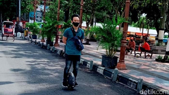 Aldo Jonathan (32) mengendarai kendaraan listrik satu roda untuk berangkat kerja. Kendaraan listrik tersebut jadi salah satu solusi untuk kurangi polusi udara.