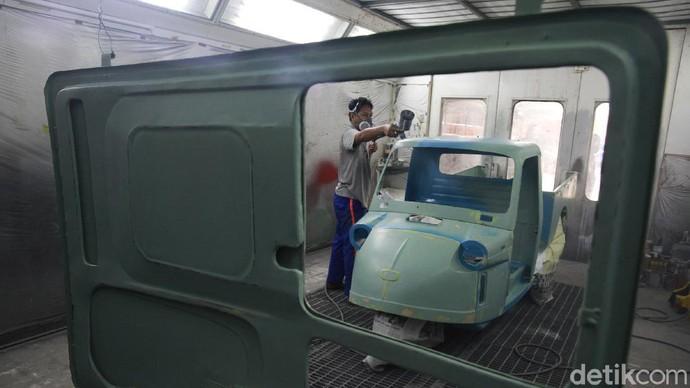 Pekerja melakukan pengecatan kendaraan bemo mesin oven khusus di workshop Layanan Prima, Jelambar, Jakarta Barat,  Jumat (20/11/2020).