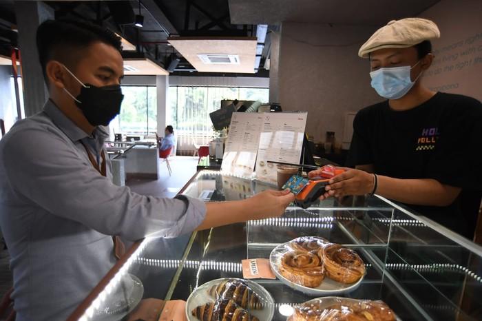 Pengunjung sebuah cafe sedang bertransaksi menggunakan kartu BNI TapCash