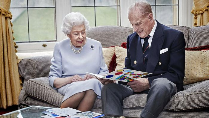 In this image released on Thursday Nov. 19, 2020, Britains Queen Elizabeth II and Prince Philip, Duke of Edinburgh look at a homemade wedding anniversary card, given to them by their great grandchildren Prince George, Princess Charlotte and Prince Louis, as the royal couple sit in the Oak Room at Windsor Castle, England, Nov. 17, 2020, ahead of their 73rd wedding anniversary.  Elizabeth married Philip on Nov. 20, 1947, at Westminster Abbey in London. Prince George, Princess Charlotte and Prince Louis are the children of Prince William and Catherine, Duchess of Cambridge, and great-grandchildren to Queen Elizabeth and Prince Philip. (Chris Jackson/Pool via AP)