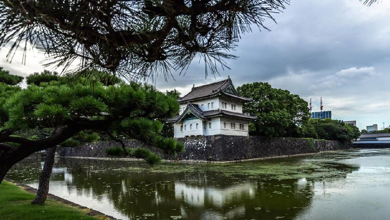 Exterior walls and tower of Tokyo Imperial Palace reflected in water. Tokyo, Japan, August 2019