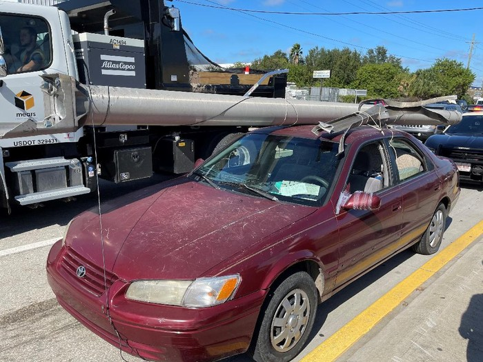 In this photo provided by the Florida Highway Patrol a downed power pole is strapped to the roof of a car, Monday, Nov. 16, 2020, on Interstate 4, in Hillsborough County, Fla. A state trooper pulled over a maroon Toyota Camry with a metal light pole, longer than the car itself, strapped to the roof on a Tampa road Monday morning, according to a Florida Highway Patrol report. The Camrys driver, Douglas Allen Hatley, told troopers that he had found the pole on the ground by the side of the highway and had planned to sell the metal for scrap, according to the report.   Hatley charged with grand theft was being held on $2,000 bond. (Florida Highway Patrol via AP)