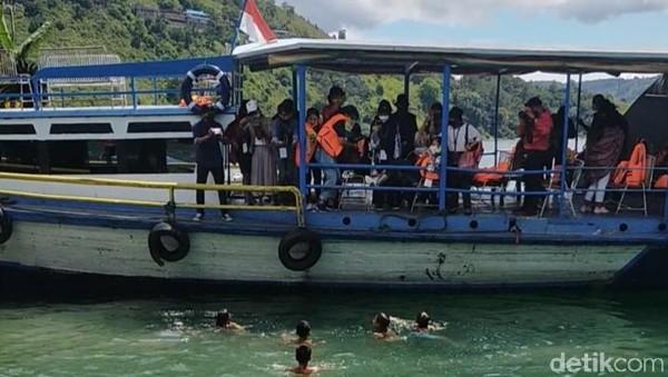 Ketika kapal menepi, terlihat beberapa bocah berenang dengan asyik. Kami pun melemparkan koin ke air untuk mereka ambil.