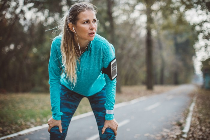 Adult running women exercise outdoor. She is exhausted after hard training, portrait
