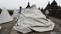Petugas menutup satu per satu stupa di candi Borobudur.