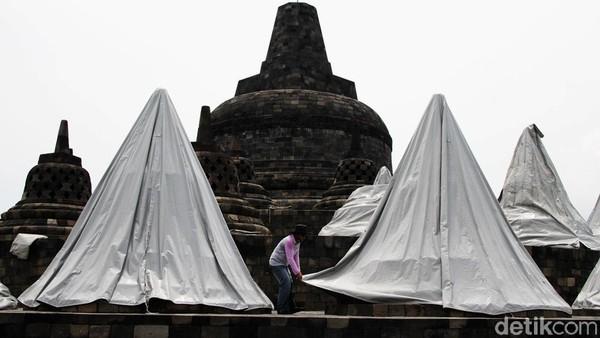 Petugas menutupi stupa candi Borobudur dengan terpal, Senin (23/11).