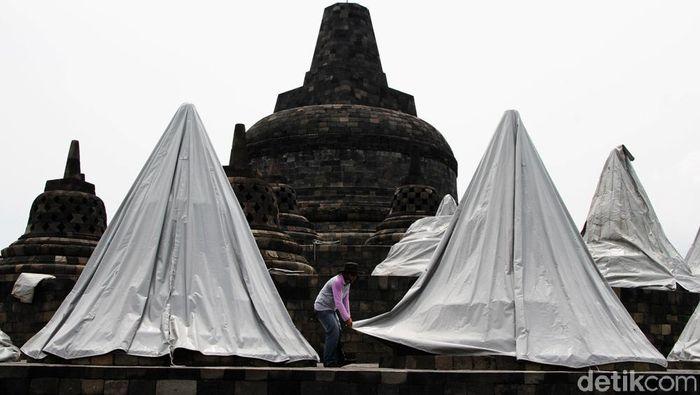 Pekerja menyelimuti stupa dengan terpal di kawasan Candi Borobudur, Magelang, Jawa Tengah, Senin (23/11). Selain penutupan stupa yang sudah berlangsung 3 minggu pihak balai Konservasi Candi Borobudur hanya membuka taman Candi Borobudur untuk umum dan pengunjung dilarang menaiki candi  selama pandemi ini hanya dihalaman candi.