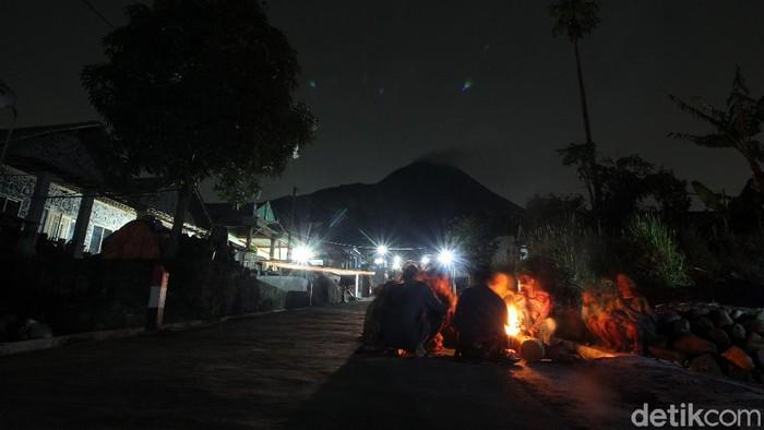 Sejumlah warga berjaga di depan rumah saat malam hari di dusun Stabelan, Tlogolele, Boyolali, Jawa Tengah, Minggu (22/11/2020). Semenjak status Gunung Merapi berubah menjadi siaga, warga di Dusun Stabelan yang berjarak 3 km dari puncak Merapi, melaksanakan jaga malam.