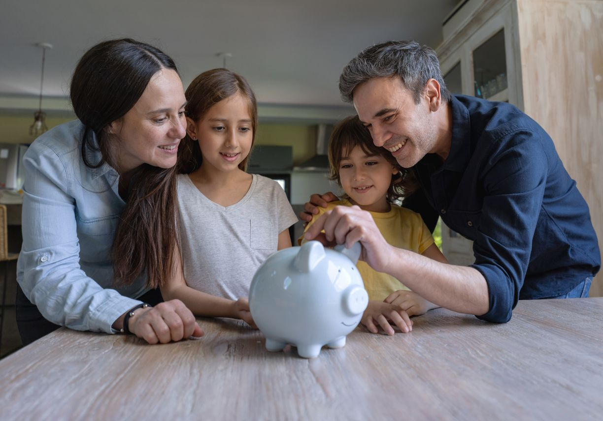 Loving latin american parents teaching their kids to save money in a piggy bank all smiling