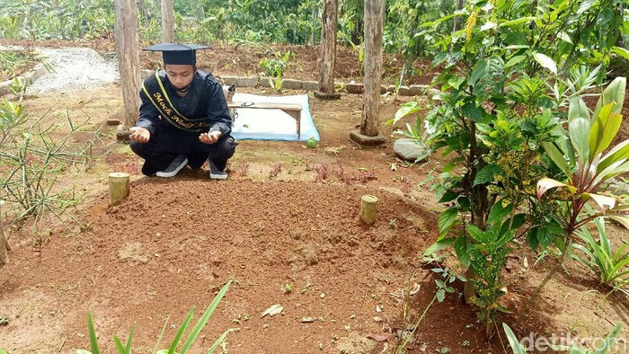 Mochamad Nadif Nasrulloh (23) mengikuti wisuda virtual di depan makam bapaknya, Desa Sidarata, Banjarnegara, Selasa (24/11/2020)