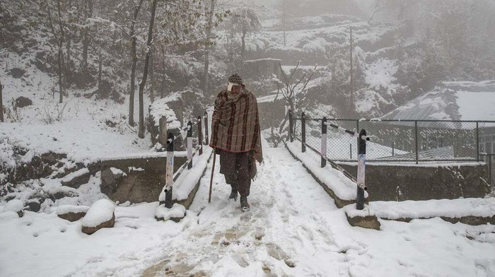 Kashmir villagers walk on a snow covered road during the season's first snowfall on the outskirts of Srinagar, Indian controlled Kashmir, Monday, Nov. 23, 2020. (AP Photo/Dar Yasin)