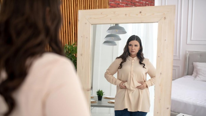 Need to keep a diet. Young woman in a beige blouse touching her belly