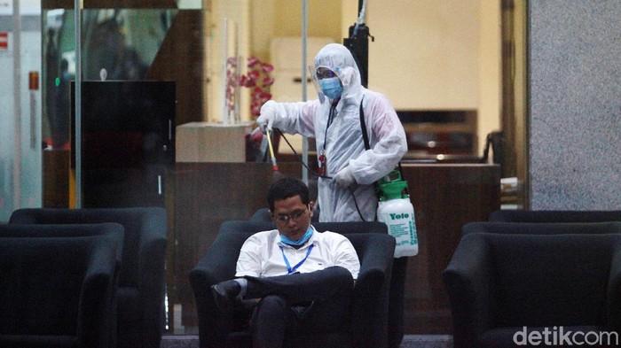 Petugas menyemprotkan cairan disinfektan di lobi gedung KPK hingga ruang wartawan, di Gedung Merah Putih, Jakarta, Rabu (25/11/2020). Penyemprotan rutin dilakukan setiap hari setelah jam kantor selesai.