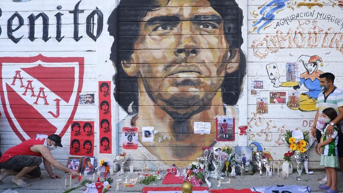 BUENOS AIRES, ARGENTINA - NOVEMBER 25: A fan mourning Diego Maradona places a picture in an altar outside Argentinos Juniors Diego Maradona Stadium on November 25, 2020 in Buenos Aires, Argentina. Diego Maradona, considered one of the biggest football stars in history, died at 60 from a heart attack on Wednesday in Buenos Aires. (Photo by Fernando de Dios/Getty Images)