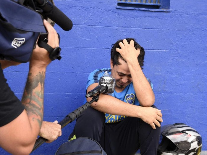 BUENOS AIRES, ARGENTINA - NOVEMBER 25: A fan cries as he is interviewed near La Bombonera stadium after the news of the death of Diego Maradona was known on November 25, 2020 in Buenos Aires. Diego Maradona, considered one of the biggest football stars in history, died at 60 from a heart attack on Wednesday in Buenos Aires.  (Photo by Fotonoticias/Getty Images)