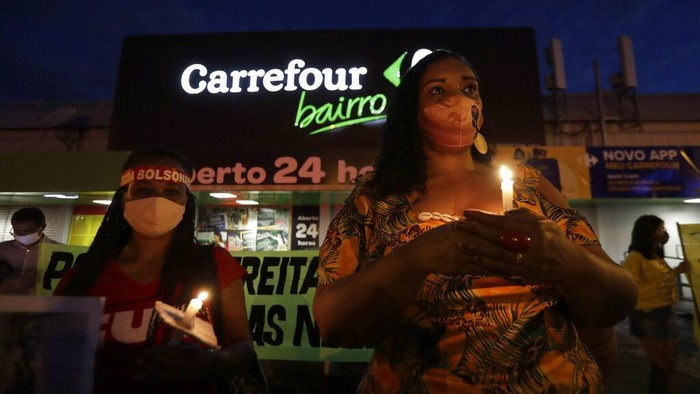 A Black Lives Matter activist wearing traditional African clothes, lights a candle during a vigil to protest the murder by security guards of Joao Albert Silveira Freitas after he broke into the Carrefour supermarket, in Brasilia, Brazil, Thursday, Nov 26, 2020. Joao Alberto Silveira Freitas died after being beaten by supermarket security guards in the southern Brazilian city of Porto Alegre on the eve of Friday's Black Consciousness Day observations, sparking outrage as videos of the incident circulated on social media. (AP Photo/Eraldo Peres)