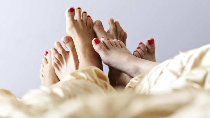 Close-up photo of feet of two women and one man lying in a bed in a hotel room.