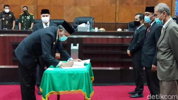 Gubernur Aceh Nova Iriansyah saat meneken berita acara persetujuan bersama terhadap Rancangan Qanun Aceh Tentang APBA 2021. (Agus Setyadi/detikcom).