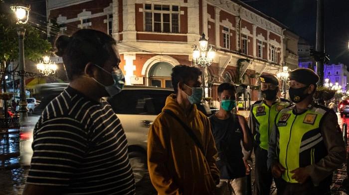 Petugas kepolisian memantau penerapan protokol kesehatan saat Operasi Yustisi COVID-19 di Kawasan Kota Lama Semarang, Jawa Tengah, Minggu (29/11/2020). Menurut data Satgas Penanganan COVID-19 per 29 November 2020, wilayah Jawa Tengah menempati peringkat pertama dalam penambahan kasus harian nasional yakni mencapai 2.036 orang sedangkan total kasus sembuh sebanyak 760 orang dan meninggal 73 jiwa, sementara itu secara nasional kasus tambahan harian mencapai 6.267 kasus dengan angka kumulatif pasien positif di Indonesia mencapai 534.266 orang. ANTARA FOTO/Aji Styawan/aww.