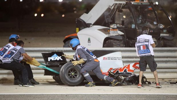 BAHRAIN, BAHRAIN - NOVEMBER 29: Track marshals clear the debris following the crash of Romain Grosjean of France and Haas F1 during the F1 Grand Prix of Bahrain at Bahrain International Circuit on November 29, 2020 in Bahrain, Bahrain. (Photo by Tolga Bozoglu - Pool/Getty Images)