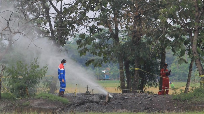 Pekerja  Pertamina EP memeriksa semburan gas liar di desa Sukaperna, Tukdana, Indramayu, Jawa Barat, Senin (30/11/2020). Semburan gas liar bercampur air dan lumpur yang sudah terjadi sejak beberapa minggu lalu itu diduga bersumber dari sumur peninggalan Belanda yang sudah tidak digunakan. ANTARA FOTO/Dedhez Anggara/hp.