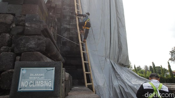 Petugas bersiap menggunakan pakaian standar keselamatan untuk naik bangunan Candi Mendut saat proses penutupan menggunakan terpaulin.