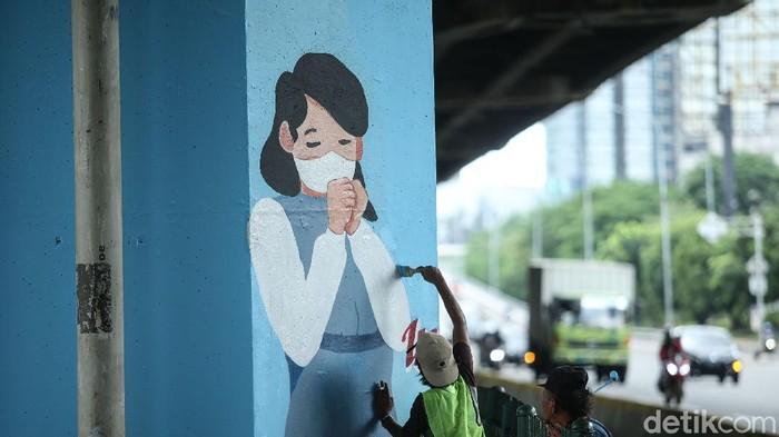 eorang seniman melukis mural di kolong Tol Wiyoto Wiyono, Jakarta Timur, Rabu (2/12/2020). Nantinya akan ada 100 tiang TOL yang akan dimural dengan gambar protokol kesehatan.