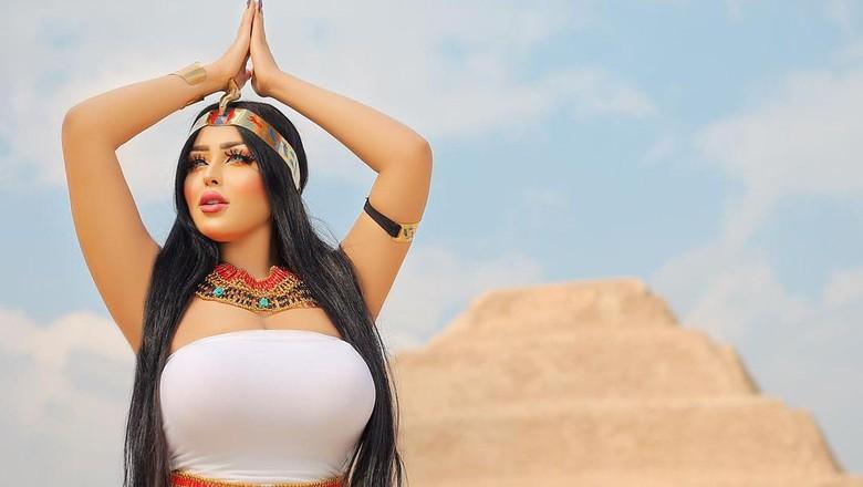 Model seksi berpose di depan piramida