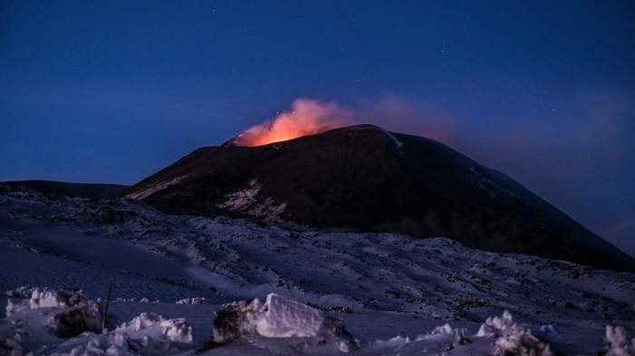 CATANIA, ITALY - DECEMBER 01: Night view of the Strombolian activity of the summit craters of the volcano Etna, photographed from an altitude of 2900 metres, with explosions and lapilli throwing visible on December 01, 2020 in Catania, Italy. Etna in activity again: two active mouths with vapour emissions, ash and frequent Strombolian explosions throwing incandescent material from the cone of the South-East Crater. (Photo by Fabrizio Villa/Getty Images)